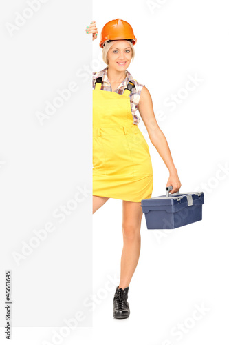 Female worker holding a tool box and posing