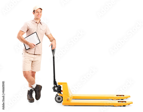 Manual worker holding a clipboard and fork pallet truck