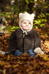 baby in autmn leaves