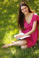 Cheerful attractive student teen girl reading book outdoor