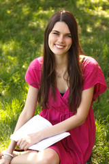 Attractive happy smiling student teen girl reading book in park