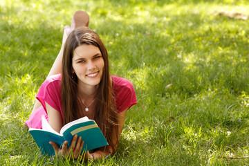 Happy student girl reading book in spring garden