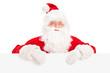 Santa Claus posing behind a blank billboard