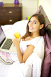 Happy woman smiling working in bed with computer