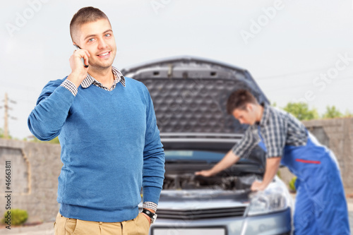 Smiling guy talking on a phone while in the background mechanic