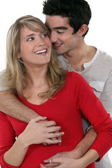 young happy couple embracing against studio background