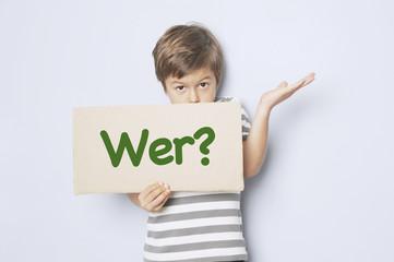 """Kind fragt mit Pappschild """"Wer?"""""""