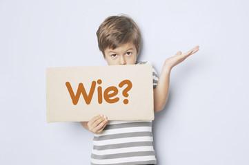 """Kind fragt mit Pappschild """"Wie?"""""""