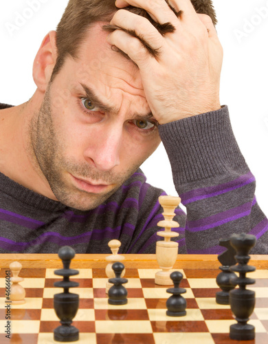 Chessboard with desperate man thinking about chess strategy, iso