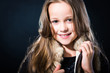 girl with fair long hair in fur vest on dark background