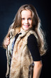 girl with fair long hair in fur vest on dark background