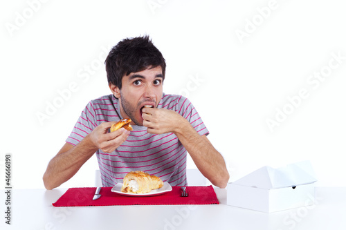 Young man eating a cake