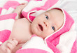 Adorable curious baby girl in pink blanket looking at the camera