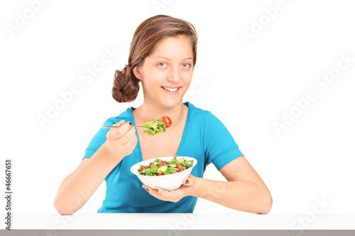 A smiling girl eating salad