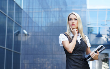 A young and attractive blond businesswoman in formal clothes