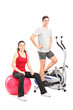 Athletic couple posing with a fitness equipment