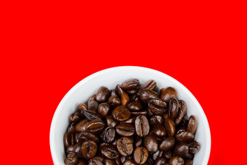 Close-up of white cup of coffee  with coffee beans on red