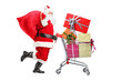 Santa Claus carrying a bag and pushing a shopping cart full of g