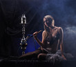 A young blond woman in erotic clothes smoking a hookah