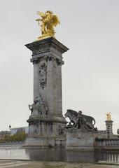 Golden Alexander the Third bridge pillars under rain in Paris