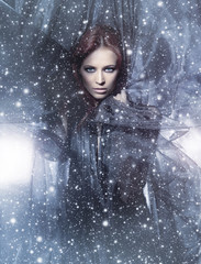 A young redhead woman posing on a snowy blue silk background