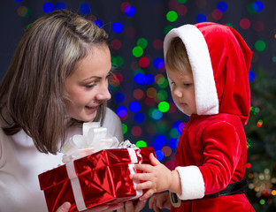 baby girl and her mother holding gift box on bright festive back