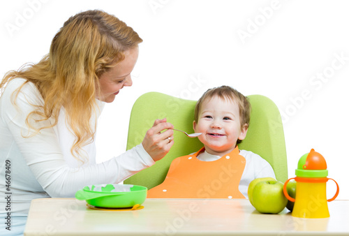 young mother spoon feeding her baby boy isolated on white