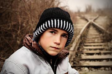 Warm gekleideter Junge auf verlassenen Gleisen