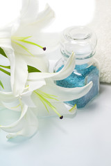 Bath blue salt and lily with towel on white background