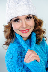 Portrait of beautiful young woman in blue knitted sweater