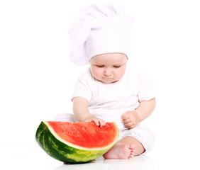 Happy baby cook eating watermelon in studio