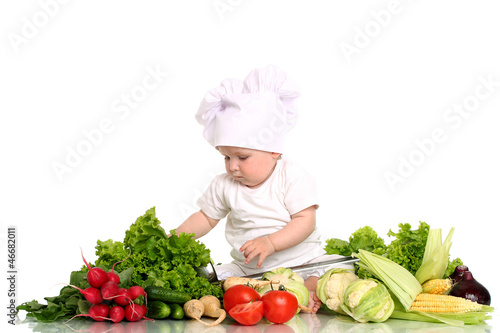 Baby cook with fresh vegetables on a white