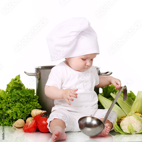 Baby cook with pan and vegetables on a white