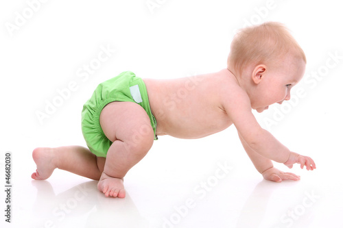 Cute little baby in green diapers in motion