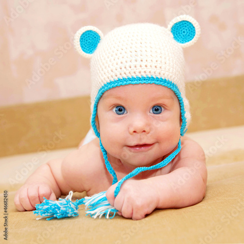 smiling baby with blue eyes wearing funny handmade cap