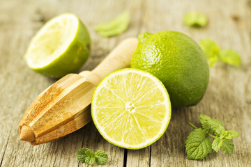 Fresh limes with a reamer on wooden table
