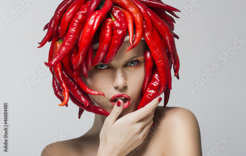 Fashion trendy woman with red chili pepper as a headwear