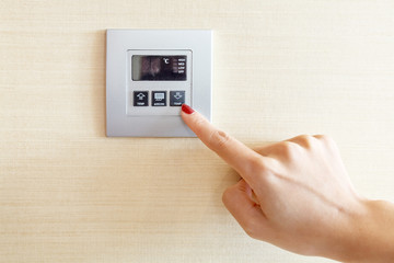 Womans hand with finger on air conditioner switch control