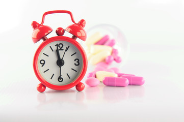 Red clock and medicine tablet on white blackground
