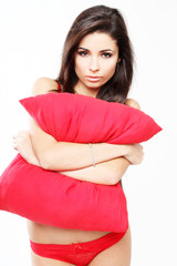 Sensual girl in red undewear playing with pillow