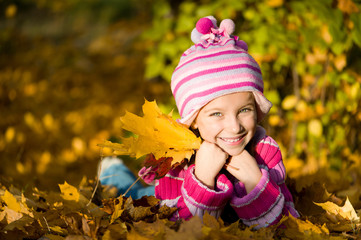 little girl lie on the leaves