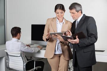 Geschäftsleute mit Tablet PC und Terminkalender