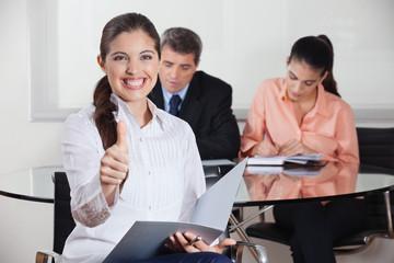 Lachende Frau mit Unterlagen im Büro
