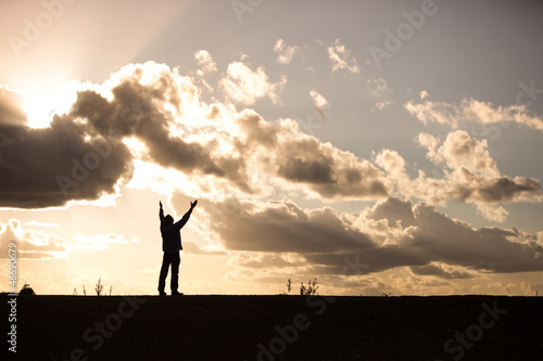 silhouette of a man with arms raised in worship