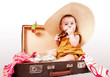 Funny baby girl sitting in old suitcase