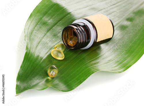 tablets on green leaf with bottle isolated on white