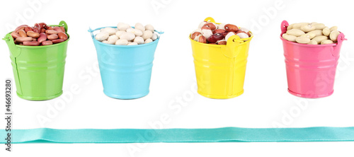 Different types of beans in colored buckets isolated on white