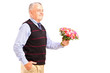A gentleman holding a bunch of flowers
