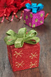 Christmas gifts with ribbons on wooden texture closeup.