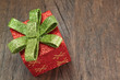 Christmas gift box with a bow on a wooden texture closeup.